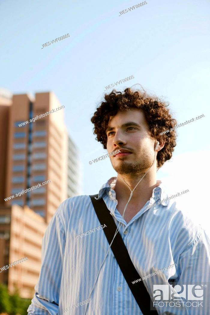 Stock Photo: Germany, Berlin, Young man listening to MP3-Player, portrait, close-up.