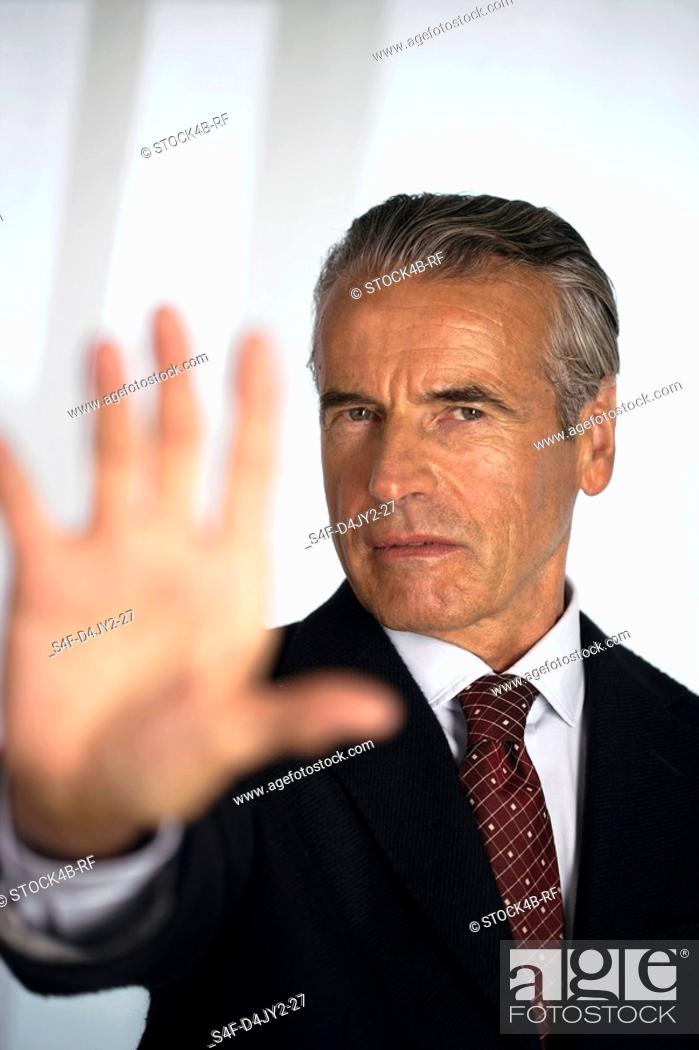 Stock Photo: Senior businessman holding hand at camera.