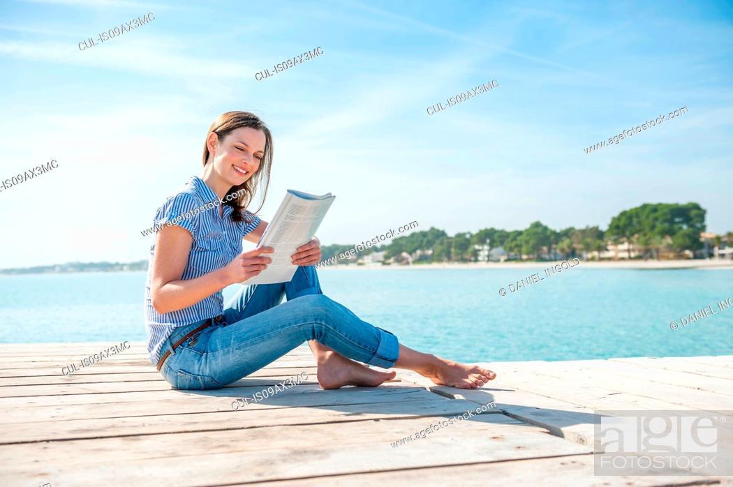 Stock Photo: Mid adult woman sitting on pier, reading magazine.