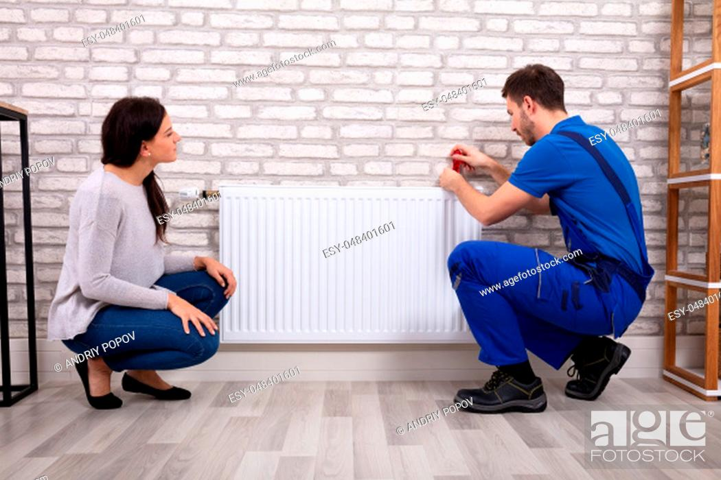 Stock Photo: Beautiful Woman Looking At Young Male Plumber In Uniform Installing Radiator With Screwdriver.