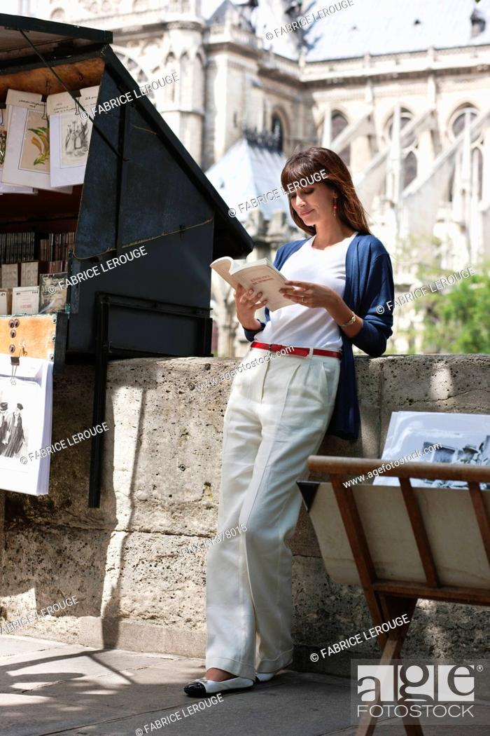 Stock Photo: Woman reading a book at a book stall, Notre Dame de Paris, Paris, Ile-de-France, France.