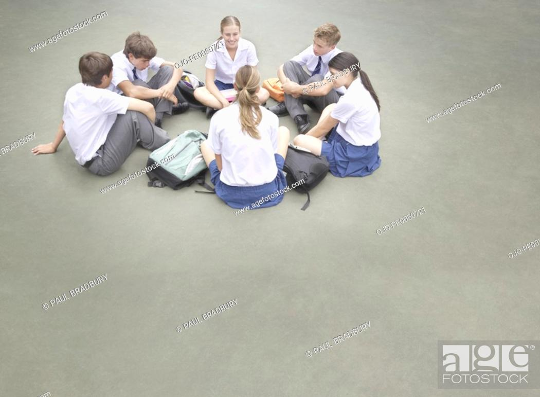 Stock Photo: Students outside their school sitting in a circle.