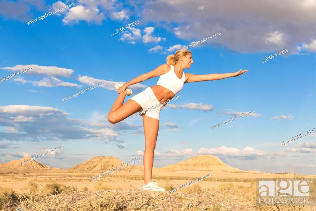 Imagen: woman exercises in the desert.
