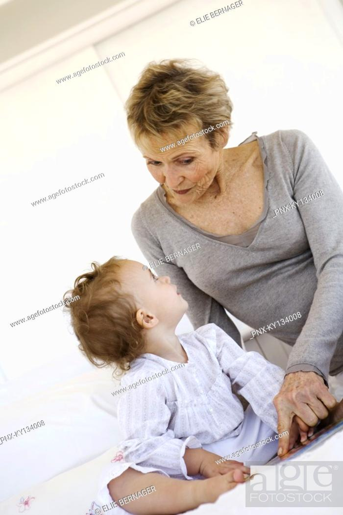 Stock Photo: Senior woman with little girl on bed.