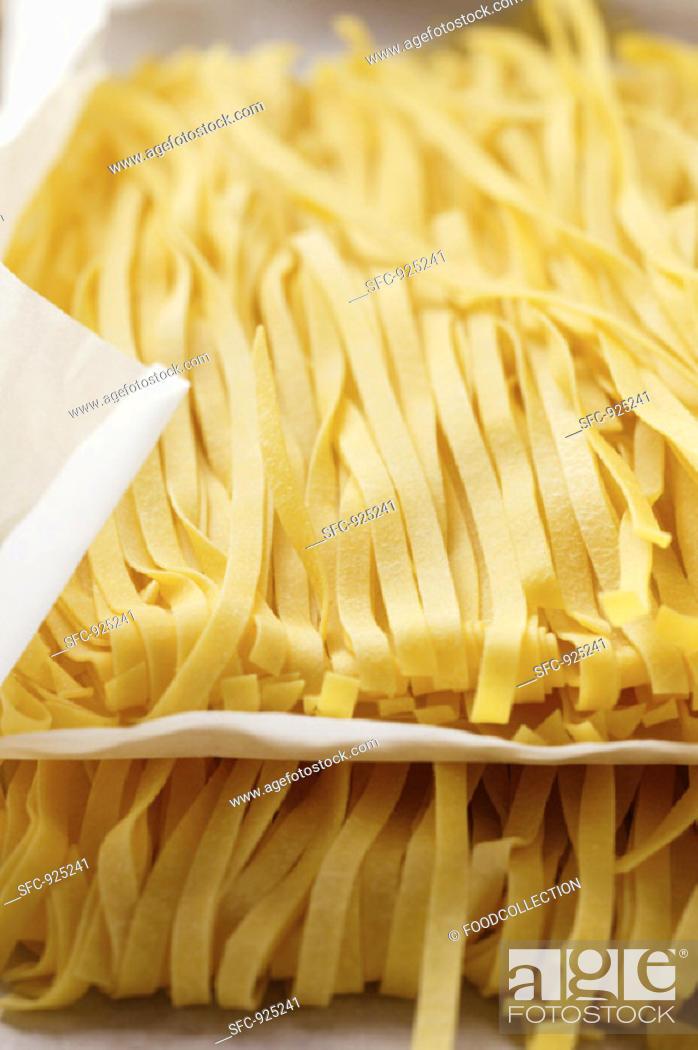 Stock Photo: Ribbon pasta on paper.