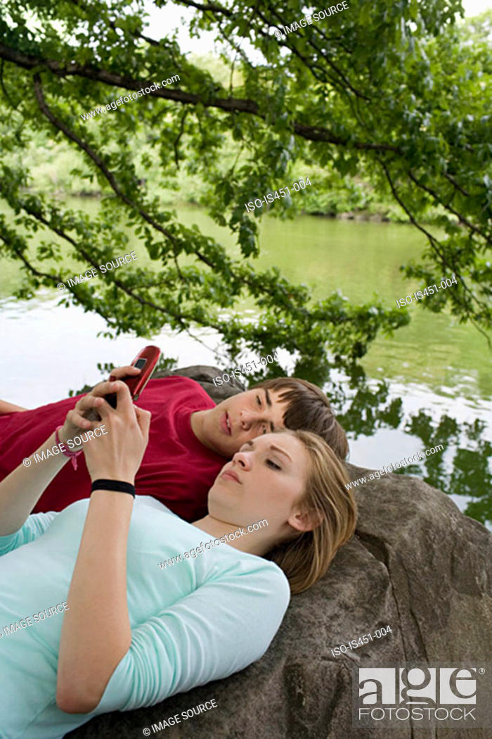 Stock Photo: Teenage couple using a cellular telephone.