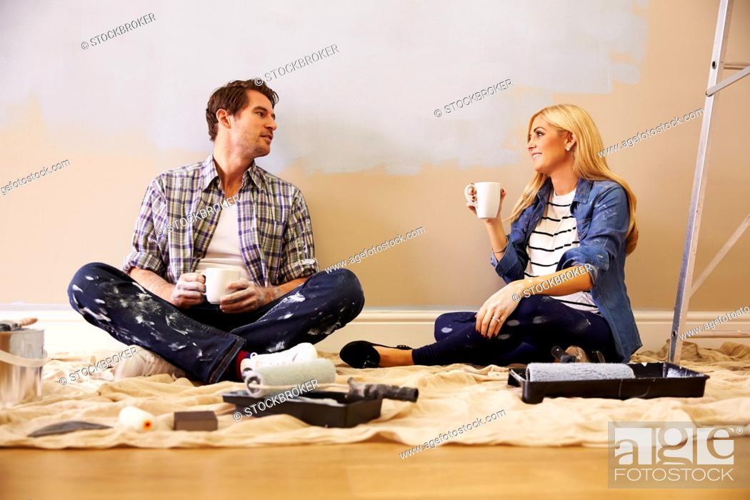 Stock Photo: Expectant Couple Taking A Break Whilst Decorating Nursery.