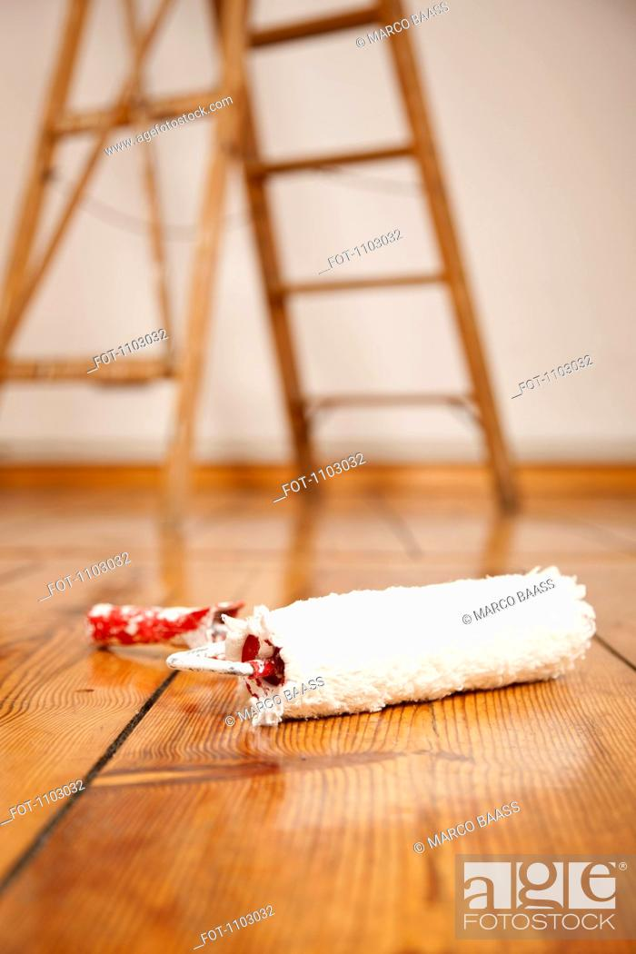 Stock Photo: A paint roller on a hardwood floor, ladder in background.