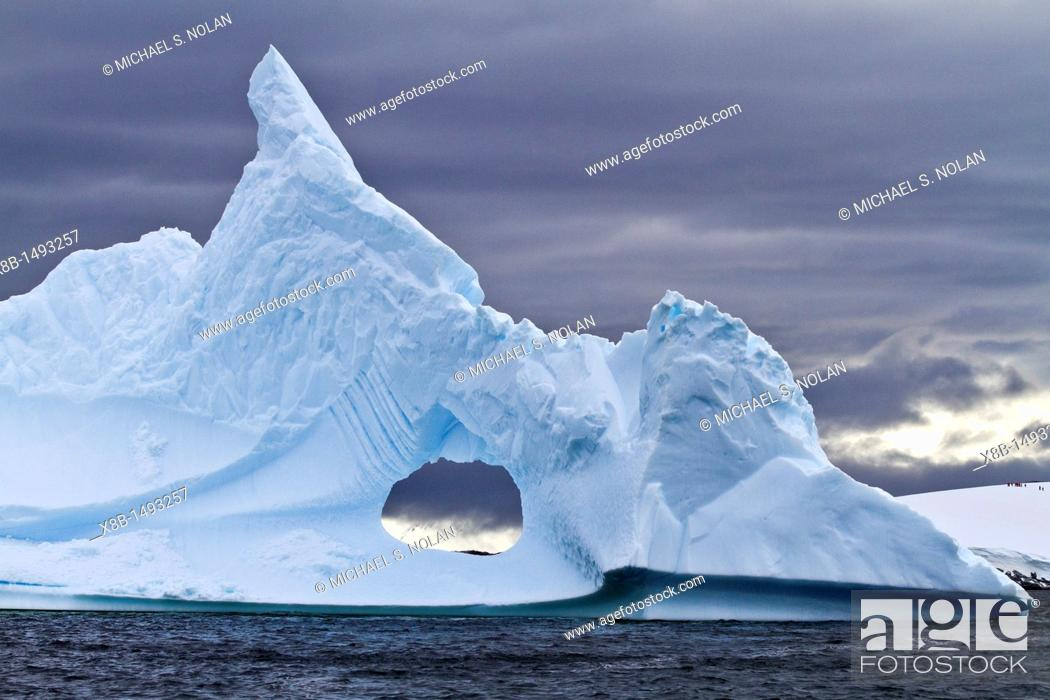Imagen: Unusual window formation in iceberg with Booth Island in the background on the western side of the Antarctic Peninsula during the summer months.