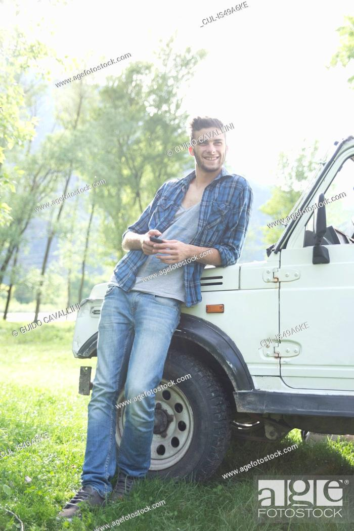 Stock Photo: Young man leaning against off road vehicle.