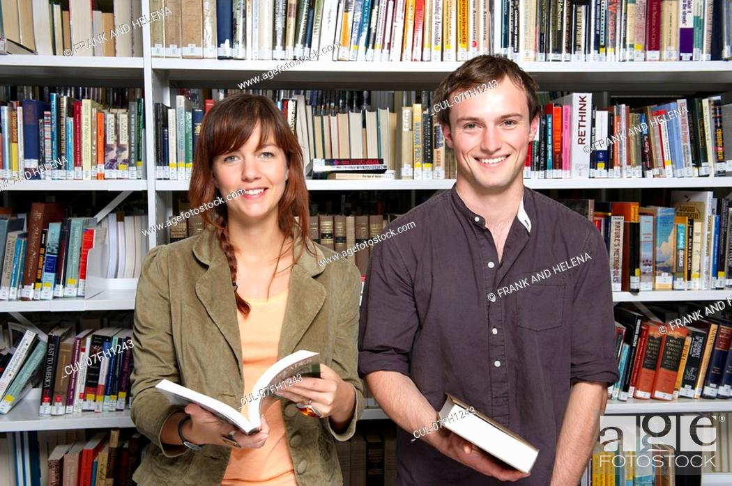 Stock Photo: Portrait of two young people in library.