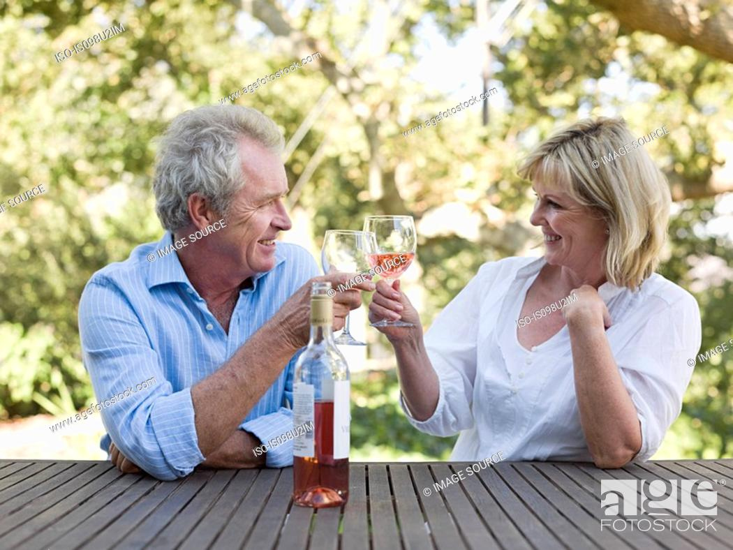 Stock Photo: Couple toasting with wine outdoors.