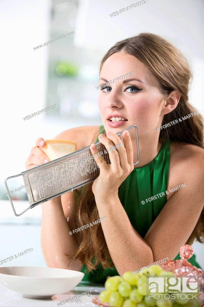 Stock Photo: Germany, Young woman grating cheese, smiling.