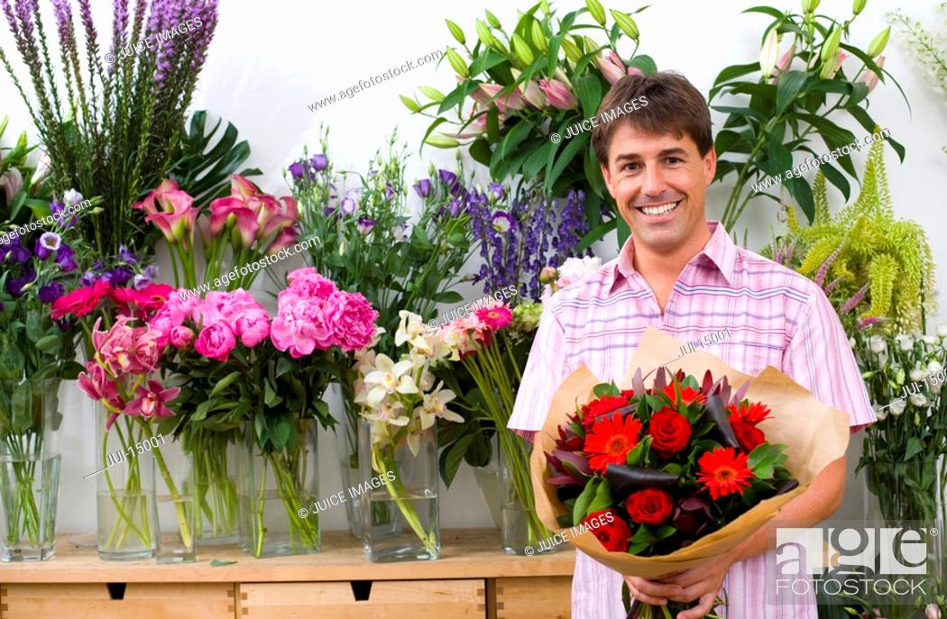 Stock Photo: Male florist with bouquet of flowers, smiling, portrait.