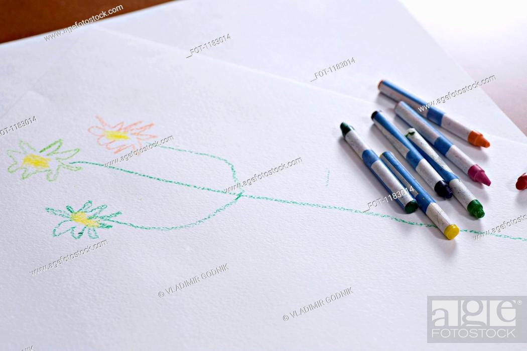 Stock Photo: Crayons lying on a child's drawing of a stem with flowers on it.