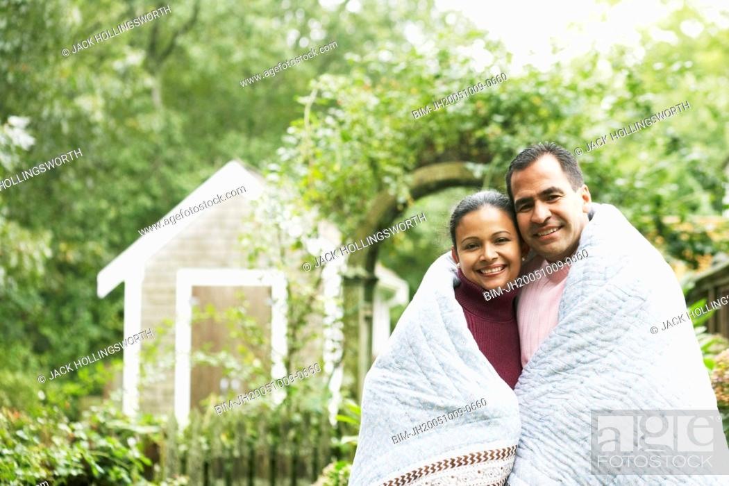 Stock Photo: Couple wrapped in a blanket outdoors.
