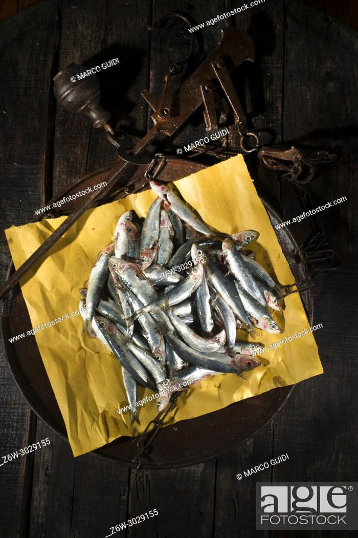 Stock Photo: Presentation of the portion of raw anchovies in an old scale dish.