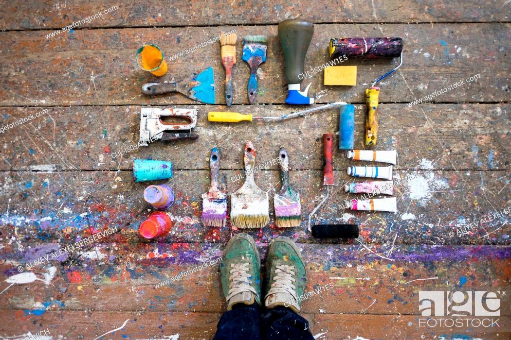 Imagen: Overhead view of artists feet and art equipment on paint splashed floorboard.
