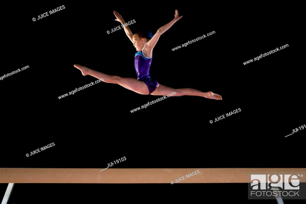 Stock Photo: Young female gymnast 9-11 performing on balance beam, low angle view.