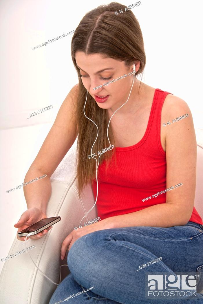 Stock Photo: Young beautiful woman using her phone as an I pod and listening to music in a white leather armchair.