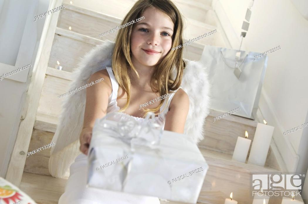 Stock Photo: Little girl holding a Christmas present, indoors.