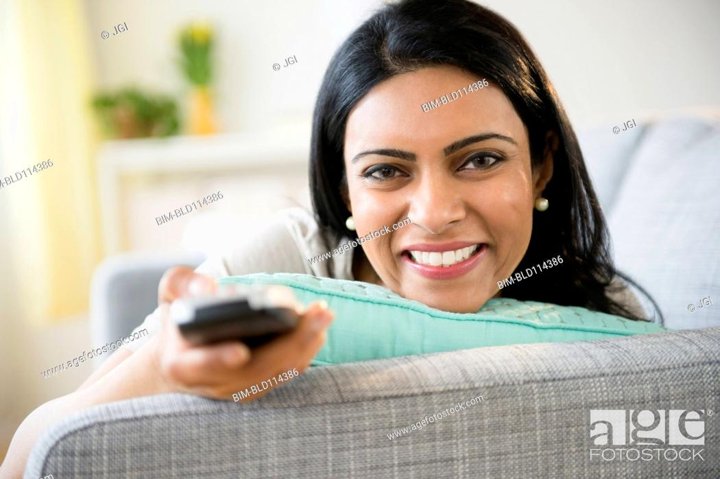 Stock Photo: Indian woman watching television on sofa.