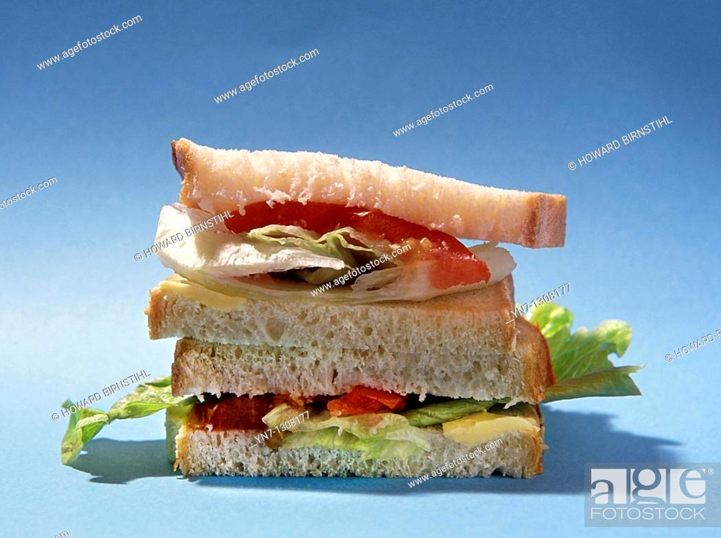 Stock Photo: close view of a salad sandwich on a plain blue background.