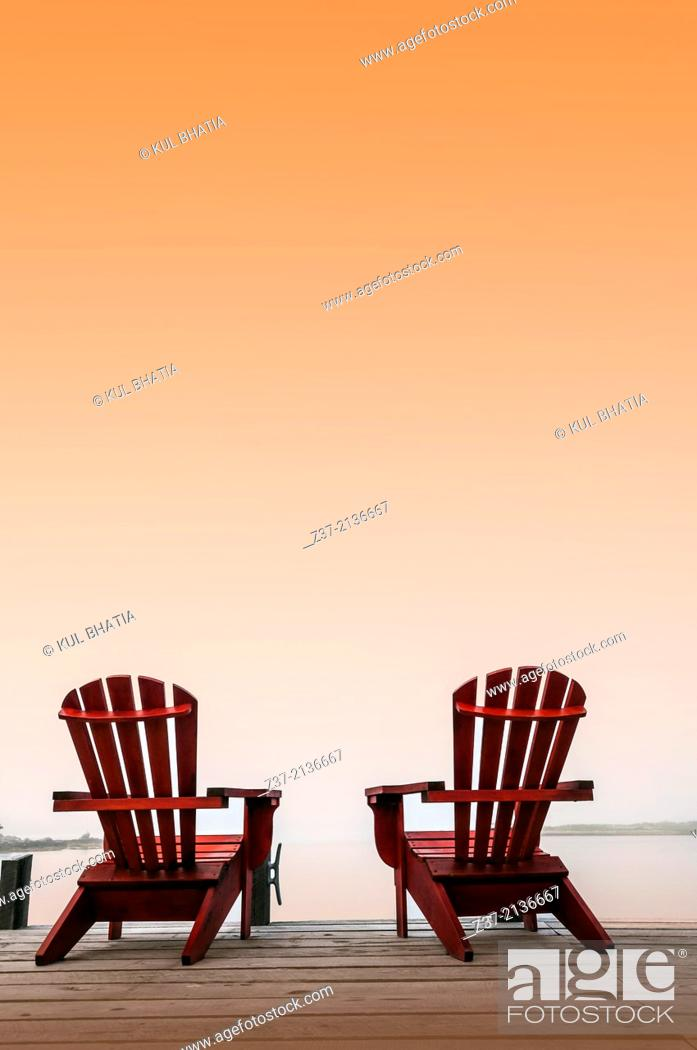 Stock Photo: Two chairs on a deck overlooking the ocean, Halifax, Canada, under a saffron sky.