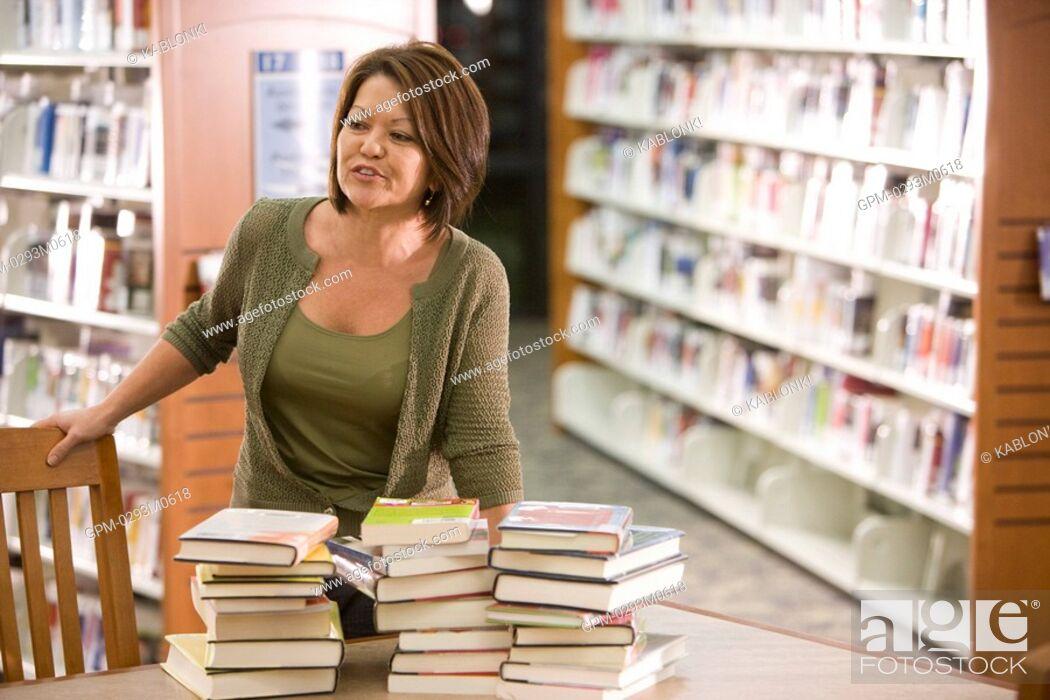 Imagen: High school teacher in library.