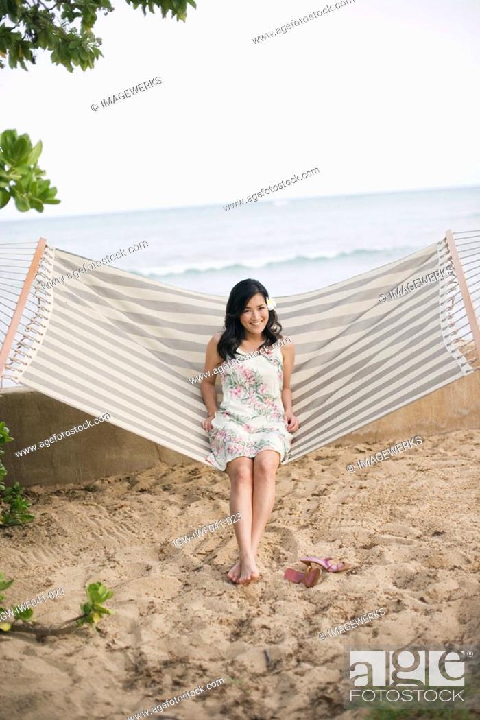 Stock Photo: A woman sitting on hammock.