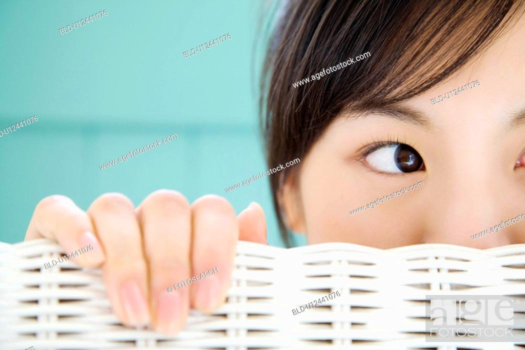 Stock Photo: Woman who lets a face peep out from a chair.