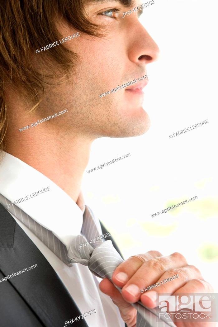 Stock Photo: Close-up of a groom adjusting his tie.