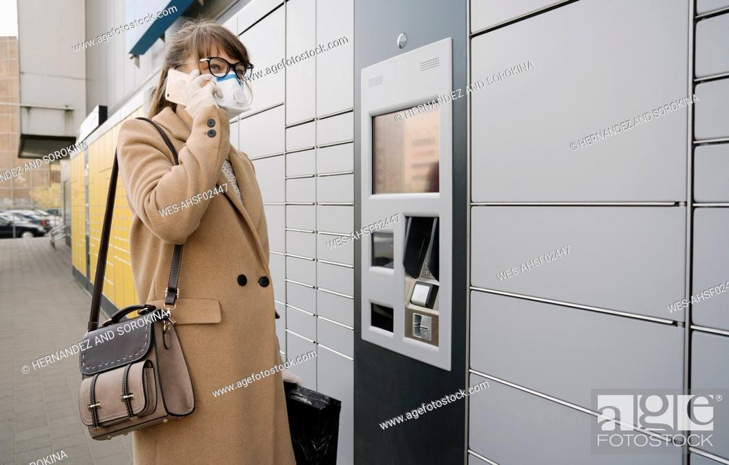 Stock Photo: Woman on the phone wearing face mask and gloves near a parcel terminal.