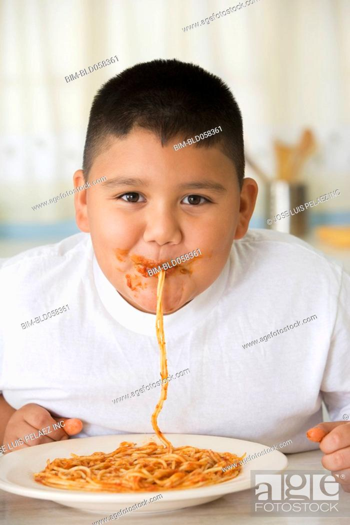 Stock Photo: Hispanic boy eating spaghetti.