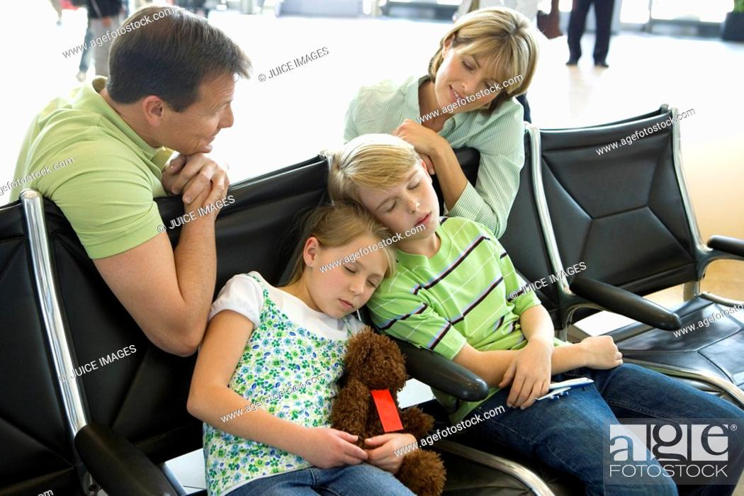Stock Photo: Parents looking at children sleeping on seats in airport departure lounge, girl 7-9 holding soft toy.
