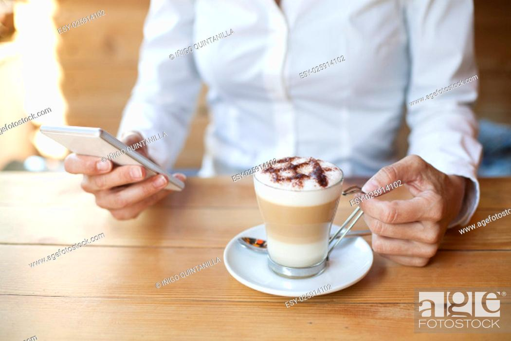 Stock Photo: woman touching mobile phone with cappuccino coffee cup on light brown wooden table cafe.