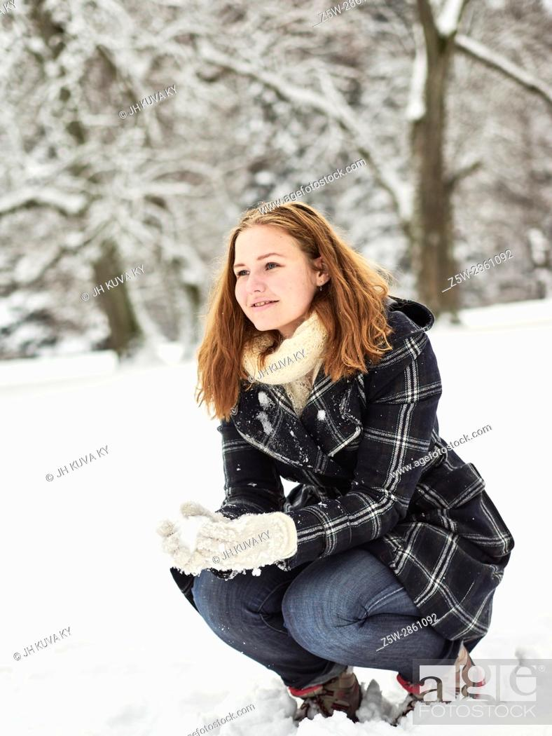 Stock Photo: Beautiful young girl wearing a winter coat and she have a snow ball in hand, Finnish winter day on February.