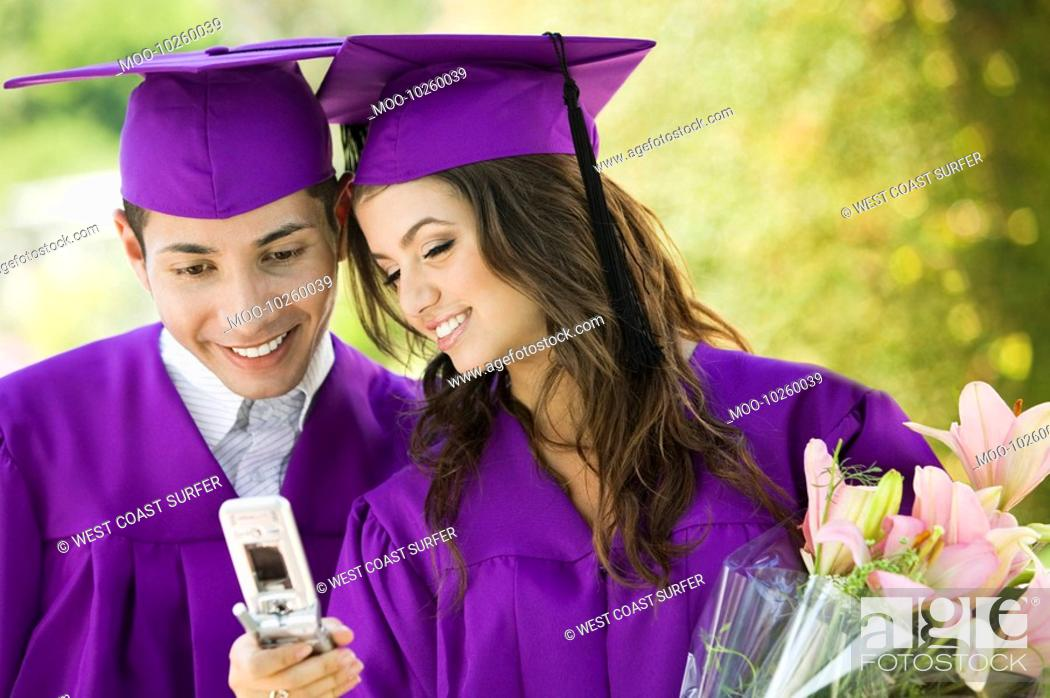 Stock Photo: Two graduates looking at cell phone outdoors.