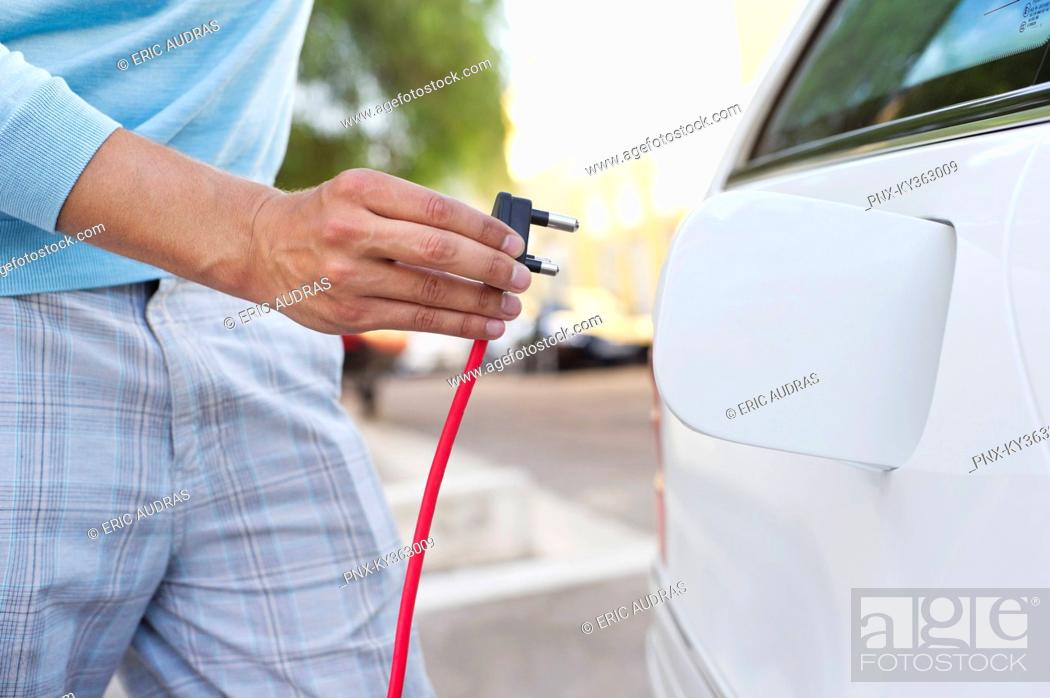Stock Photo: Mid section view of a mid adult man charging the electric car.