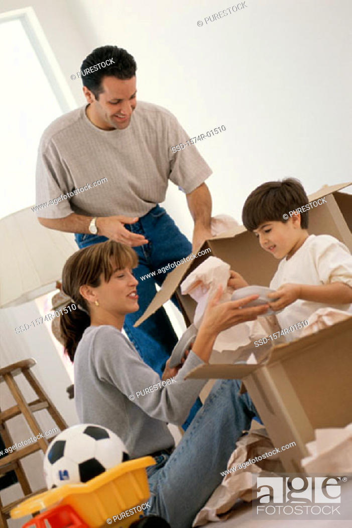 Stock Photo: Young couple unpacking boxes with their son.