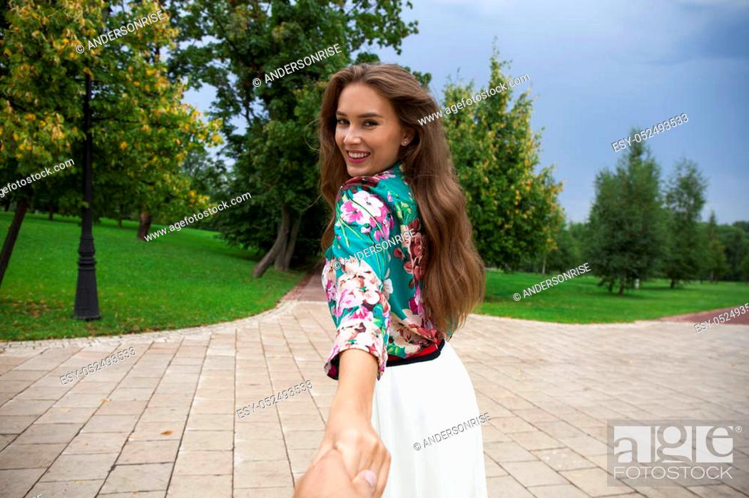 Stock Photo: Follow me, Young beautiful woman pulls the arm of her boyfriend in a city park.