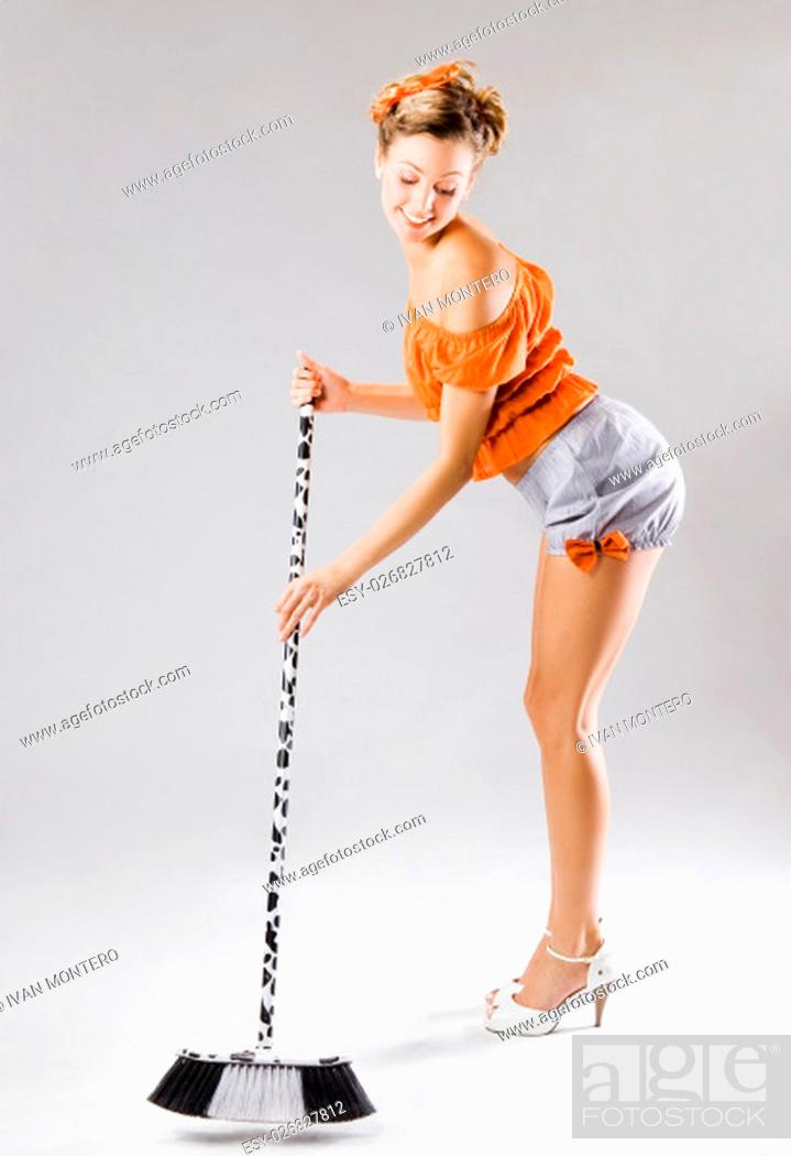 Stock Photo: pinup funny young sexy woman sweeping.