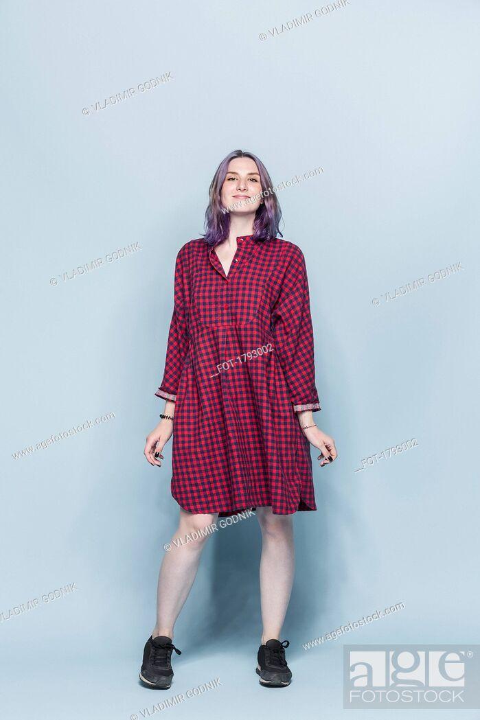 Imagen: Portrait confident and fashionable young woman against blue background.