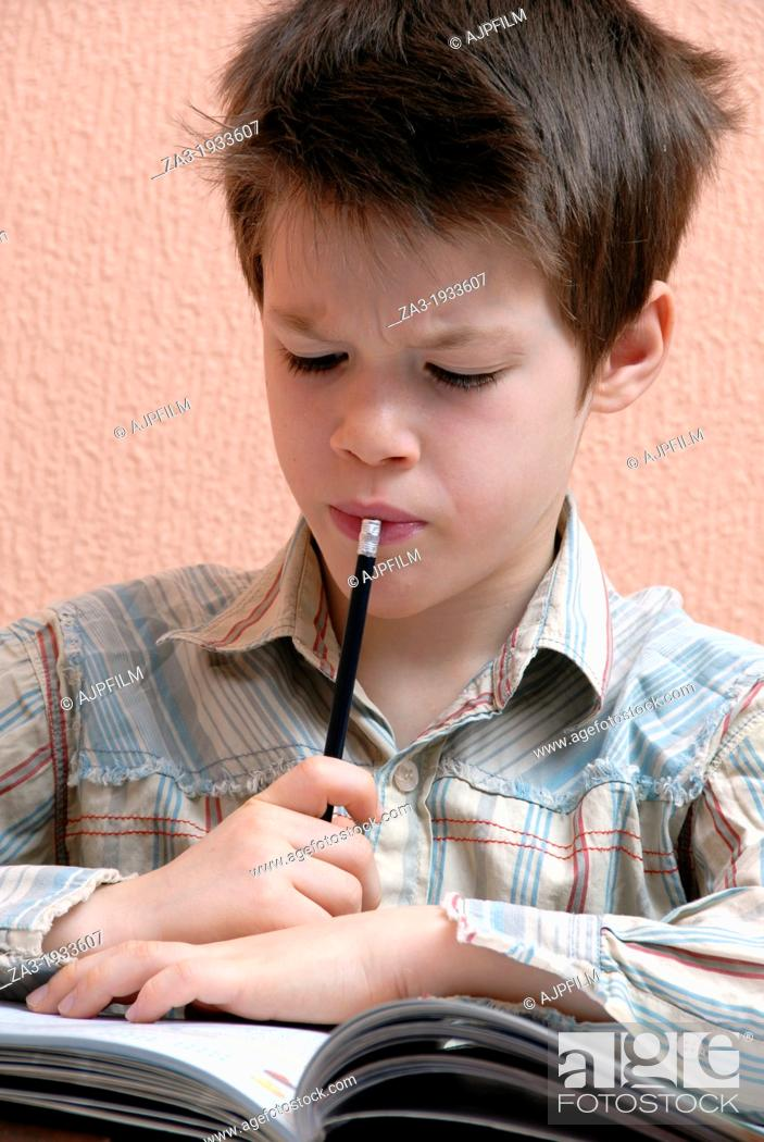 Stock Photo: Young boy doing his homework.