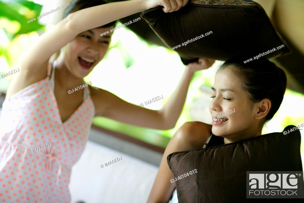 Stock Photo: View of young women pillow fighting.