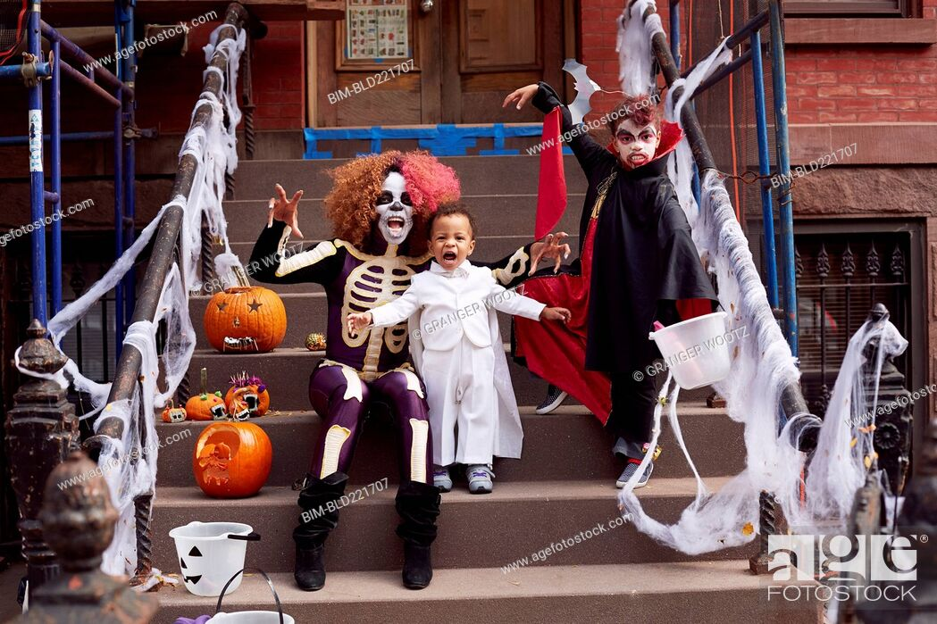 Stock Photo: Mother and children wearing Halloween costumes.