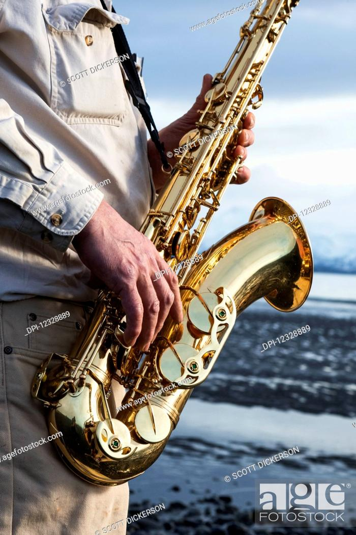 Imagen: A Man Stands With A Saxophone On The Beach At The Water's Edge; Alaska, United States Of America.