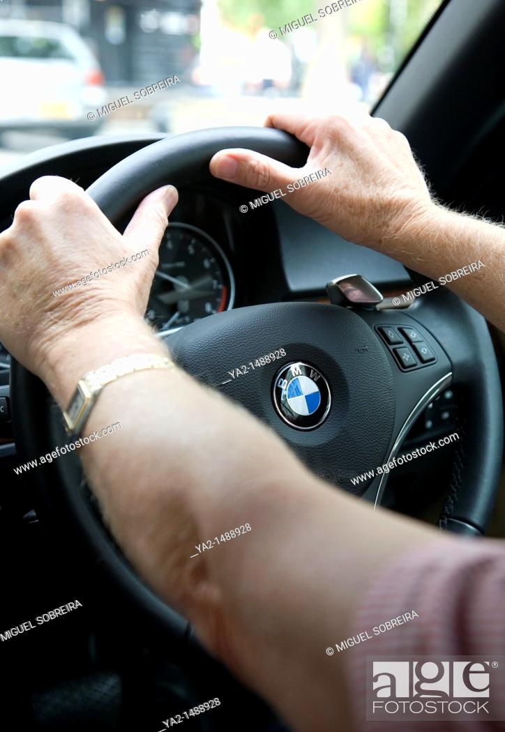Stock Photo: Mature Mans hands on steering wheel on BMW.