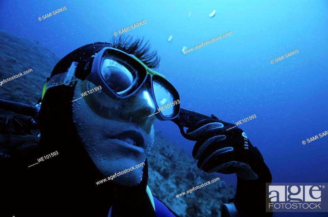 Stock Photo: One scuba diver holding a gun to his head underwater.