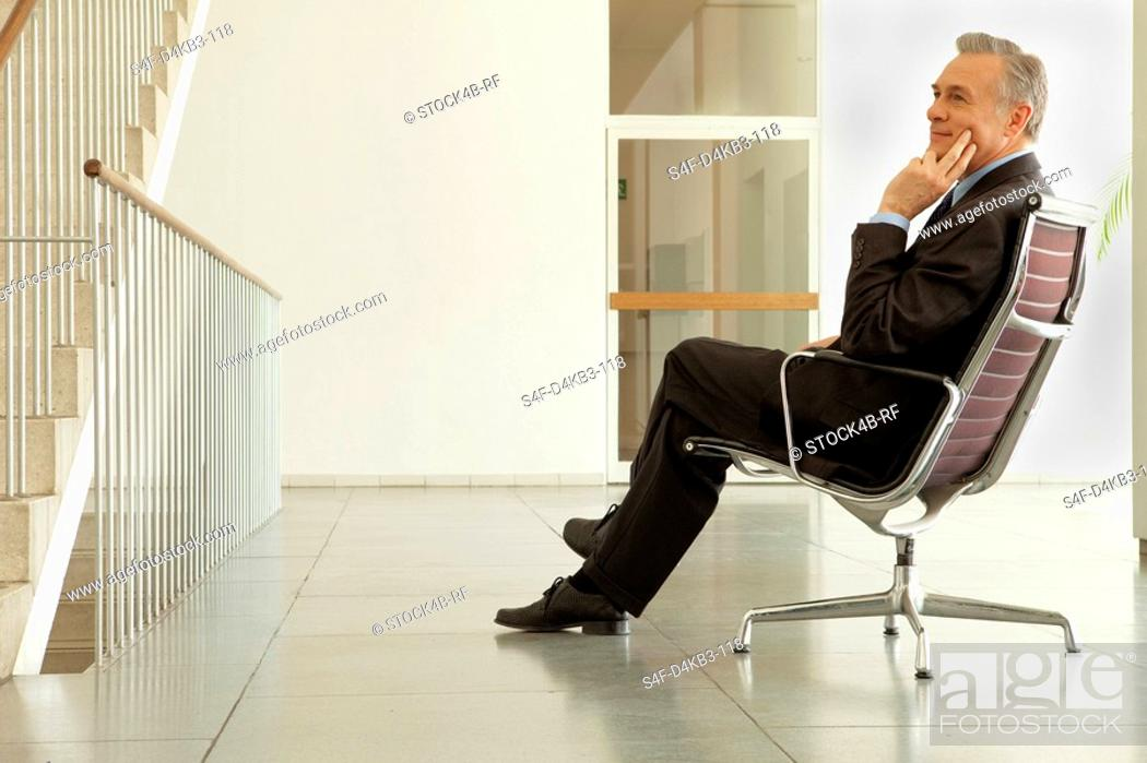 Stock Photo: Businessman sitting on office chair in hall, Munich, Bavaria, Germany.